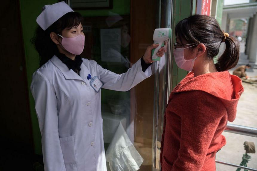 A health worker takes the temperature of a woman at a hospital in Pyongyang on April 1, 2020.