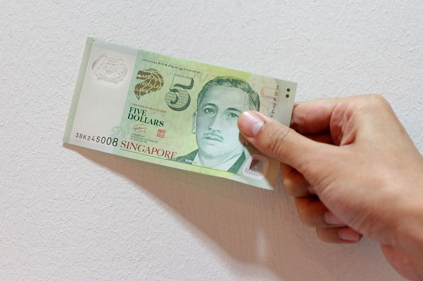 Posed photo of a hand holding a Singapore's five dollar note.