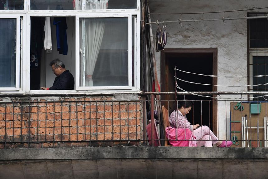 A woman looks at her mobile phone as she sits on a balcony in China, on March 10, 2020.