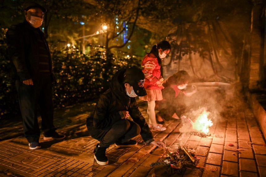 People pay respects to their ancestors on the eve of Qing Ming, in Wuhan, on April 3, 2020.