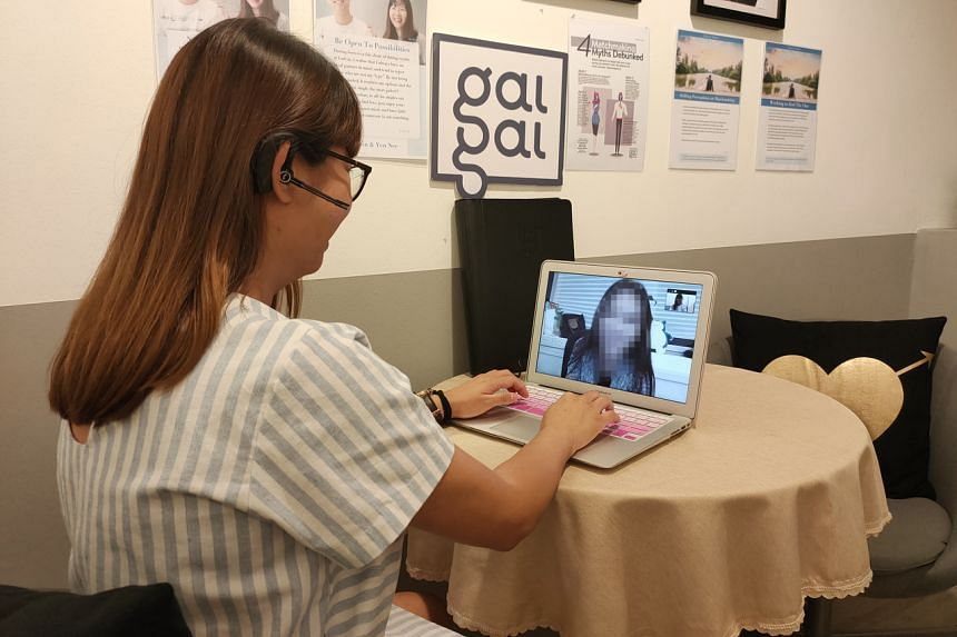 A relationship manager from dating agency GaiGai advising a client over a video call.