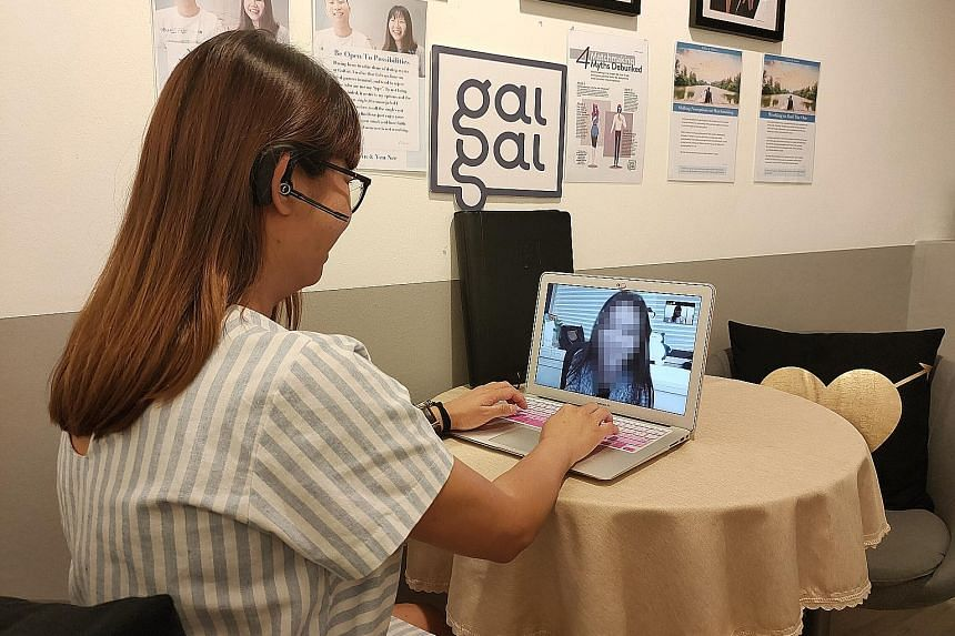 A relationship manager from dating agency GaiGai advising a client over a video call. Its members are offered the option of online dates.