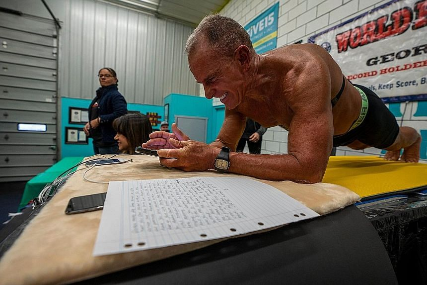 George Hood, 62, straining his way to setting the Guinness World Record for the plank on Feb 15. After recovering, he did 75 push-ups. PHOTO: FACEBOOK/JOSEFHOLICPHOTOGRAPHY