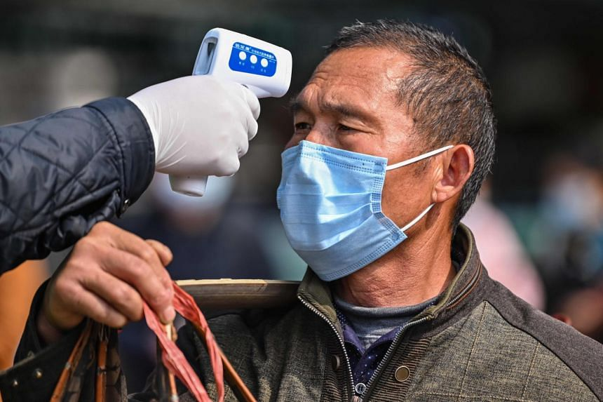 A man has his temperature checked as he leaves the Hankou railway station in Wuhan on April 4, 2020.
