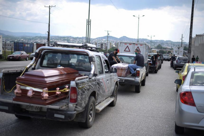 Vehicles carrying coffins lining up outside a cemetery in Guayaquil, Ecuador, on April 2, 2020.