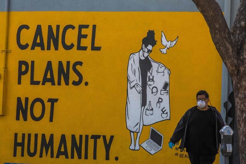 A man wearing gloves and a face mask walks by a mural in US, on April 4, 2020.