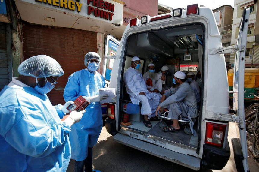 Men waiting in an ambulance that will take them to a quarantine facility in India on April 3, 2020.