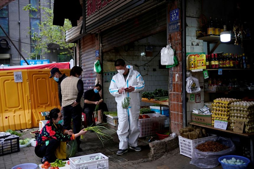 Residents buy vegetables at a grocery stall in Wuhan on April 5, 2020.