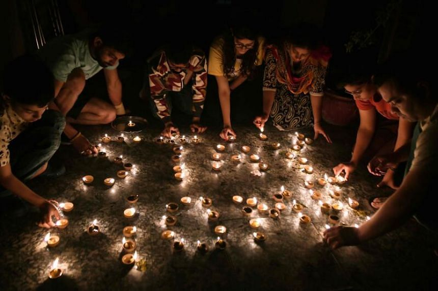 """Residents light oil lamps forming the words """"Stay Home"""" during a vigil amid the coronavirus outbreak."""