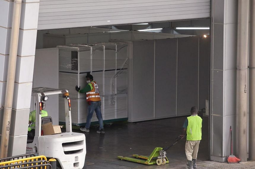 Workers moving what appears to be cabinets into Singapore Expo Hall 3 on April 6, 2020.