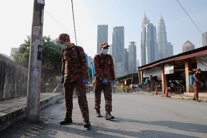 Malaysian firefighters spraying disinfectant on a street during the movement control order due to the outbreak of the coronavirus in Kuala Lumpur last Tuesday. The number of new infections detected daily since the order was declared has oscillated be