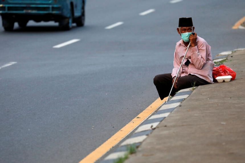 An elderly man wearing a face mask sits in Indonesia, on April 3, 2020.
