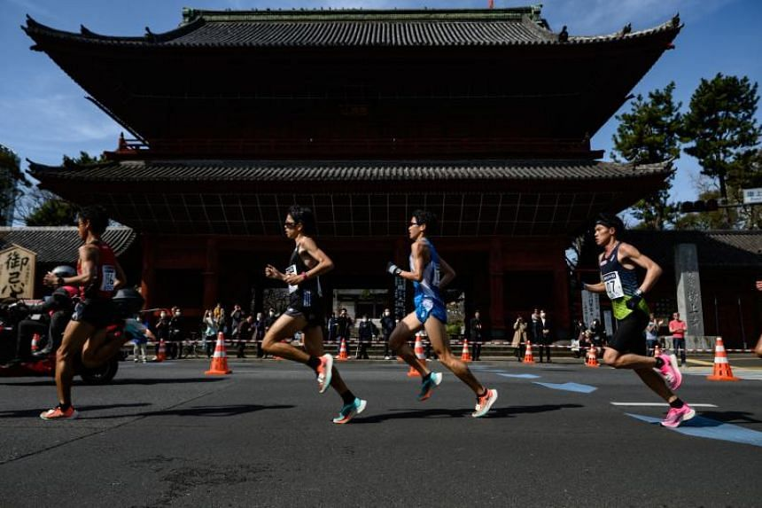 Runners pass by Shiba Park as they compete in the Tokyo Marathon on March 1, 2020.