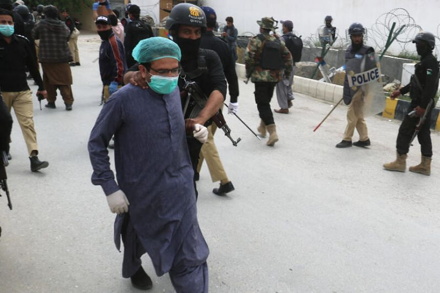 A police officer detains a doctor in Pakistan on April 6, 2020.
