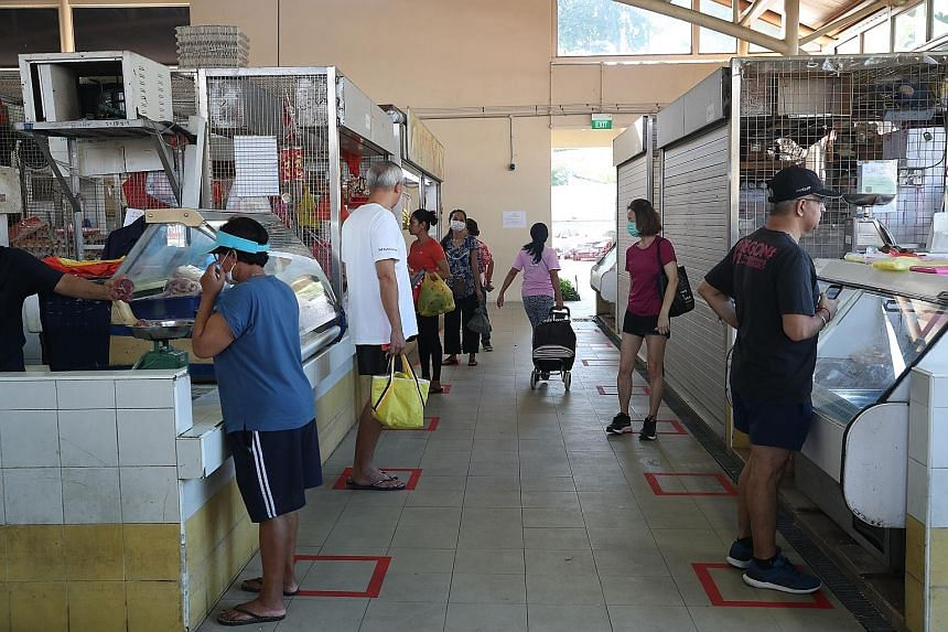People shopping at Serangoon Garden Market last Saturday. The additional payments announced yesterday, which are meant to help households cope with the impact of the coronavirus pandemic, will cost the Government an extra $1.1 billion. ST PHOTO: TIMO