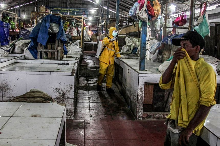 A worker wearing protective gear disinfects a traditional market in Indonesia on March 25, 2020.