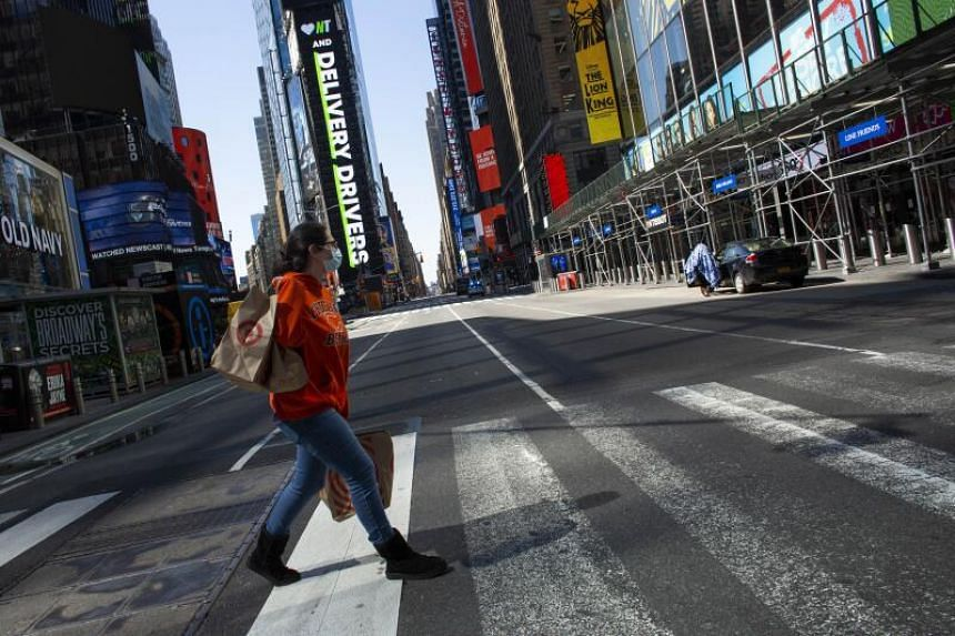 A woman crosses a road in New York City's Times Square, on April 6, 2020.