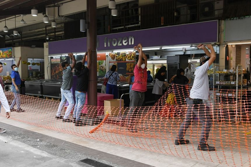 Workers setting up fences around Geylang Serai market on April 7, 2020.