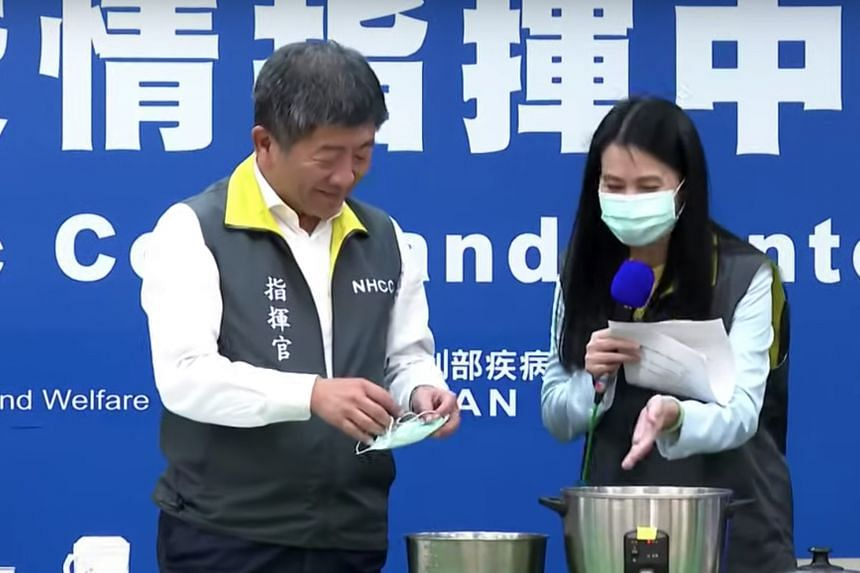 Taiwan's Health Minister Chen Shih-chung (left) demonstrates how to disinfect a mask with a steamer.