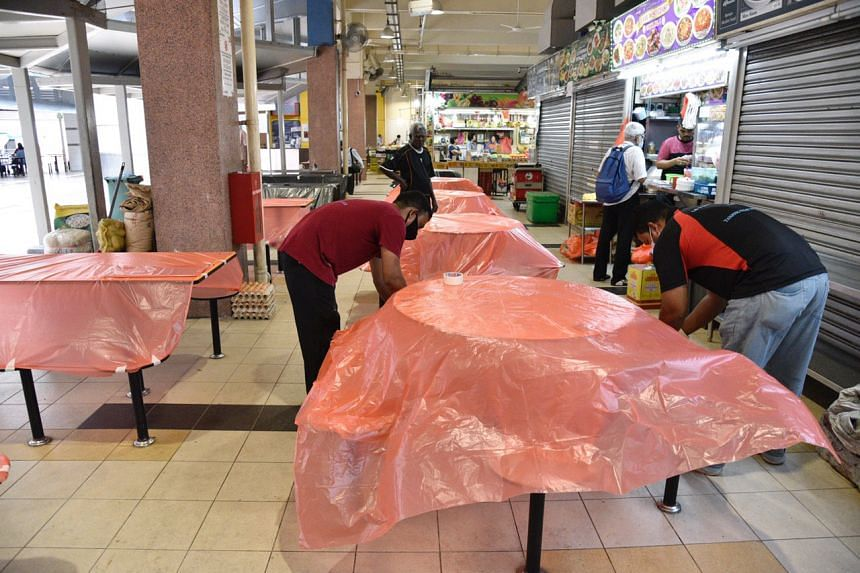 Workers covering tables at Tekka Market on April 7, 2020.