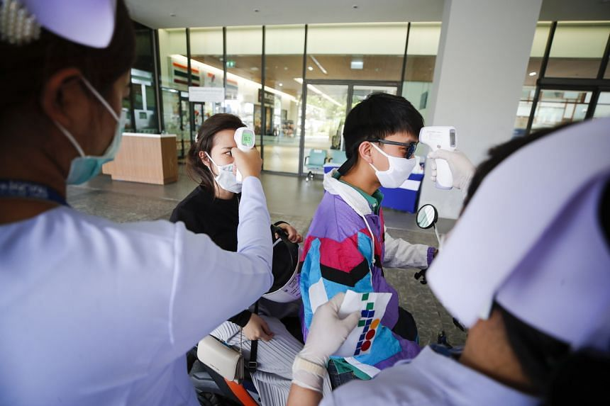People get their temperatures taken at a Covid-19 drive-through testing site in Bangkok on April 6, 2020.