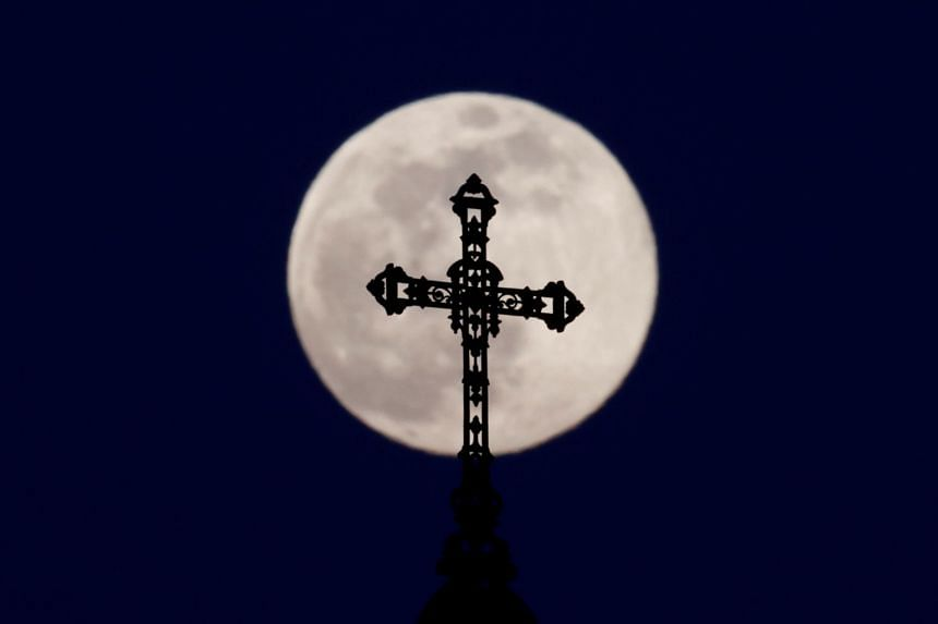 The pink supermoon rises behind the cross atop the spite of a church in Wolxheim, near Strasbourg, France.