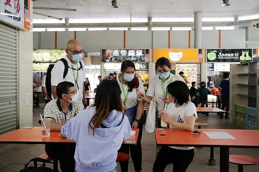 National Environment Agency officers advising members of the public on the stricter safe distancing rules at Bedok Interchange Hawker Centre yesterday. ST PHOTO: GIN TAY