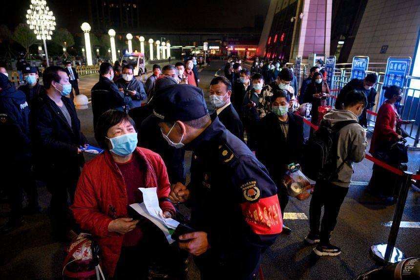 Passengers wear face masks as they form a queue at the Wuhan Wuchang Railway Station in Wuhan, early on April 8, 2020.