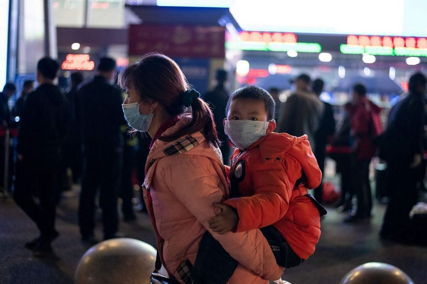 Passengers wear face masks as they form a queue at Wuhan Wuchang Railway Station in Wuhan, early on April 8, 2020,