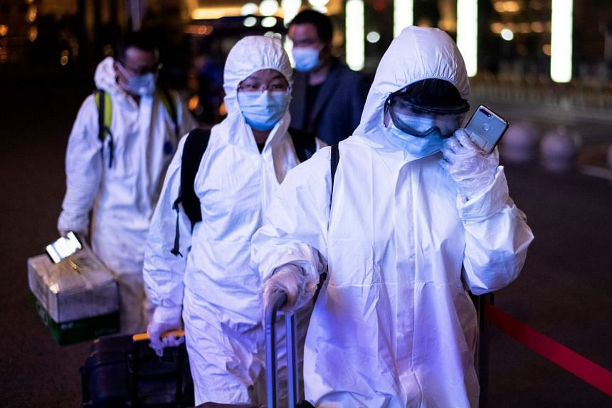 Passengers wear hazmat suits as they arrive at Wuhan Wuchang Railway Station in Wuhan, to leave the city early on April 8, 2020.