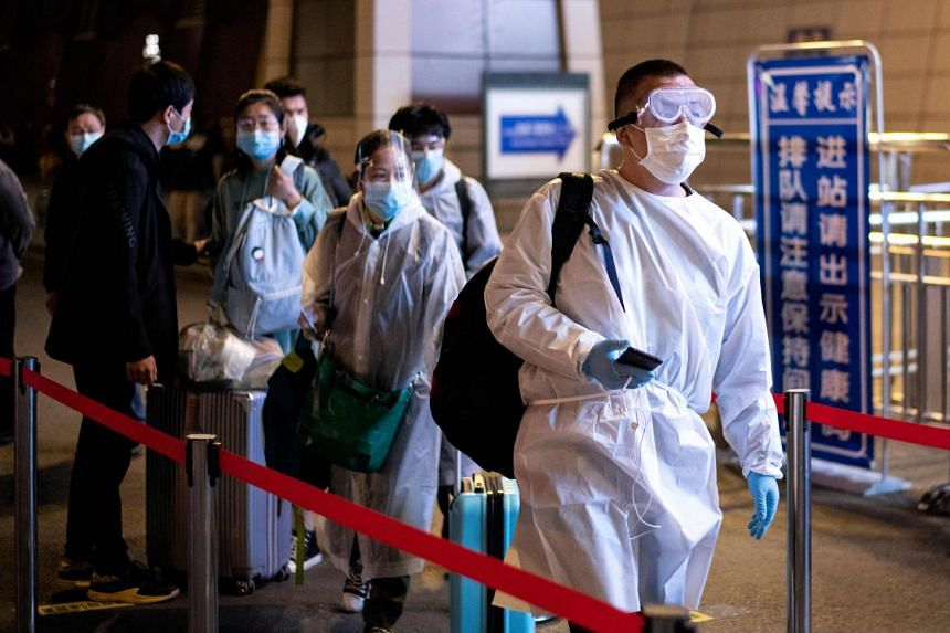 Passengers wear hazmat suits as they arrive at Wuhan Wuchang Railway Station in Wuhan, to leave the city.