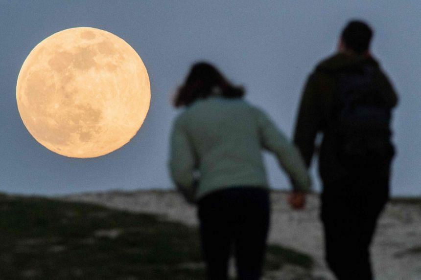 A couple hold hands as they walk to watch the Supermoon come up in Hanover, western Germany.