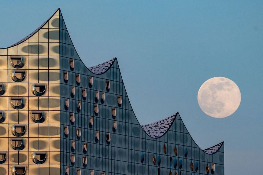 The Supermoon comes up behind the Elbphilharmonie concert hall in Hamburg, northern Germany.