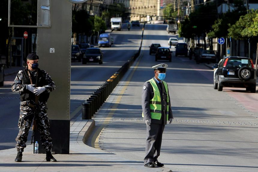 A Lebanese police officer wearing a mask stands guard in Sidon, Lebanon, on March 22, 2020.