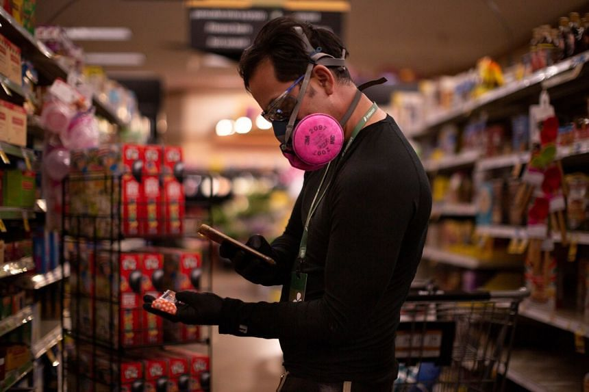A grocery store employee uses his phone to scan an item for a delivery order in Tucson, Arizona.