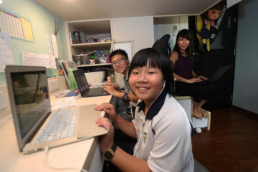 Kevin Yu, seven, doing his schoolwork at home yesterday, accompanied by his sister Nicole, four. PHOTO: COURTESY OF YU JIARONG Ms Yvonne Kong-Ho doing her work while keeping an eye on her children Gabriel and Natalie, who are in Primary 5 and Primary