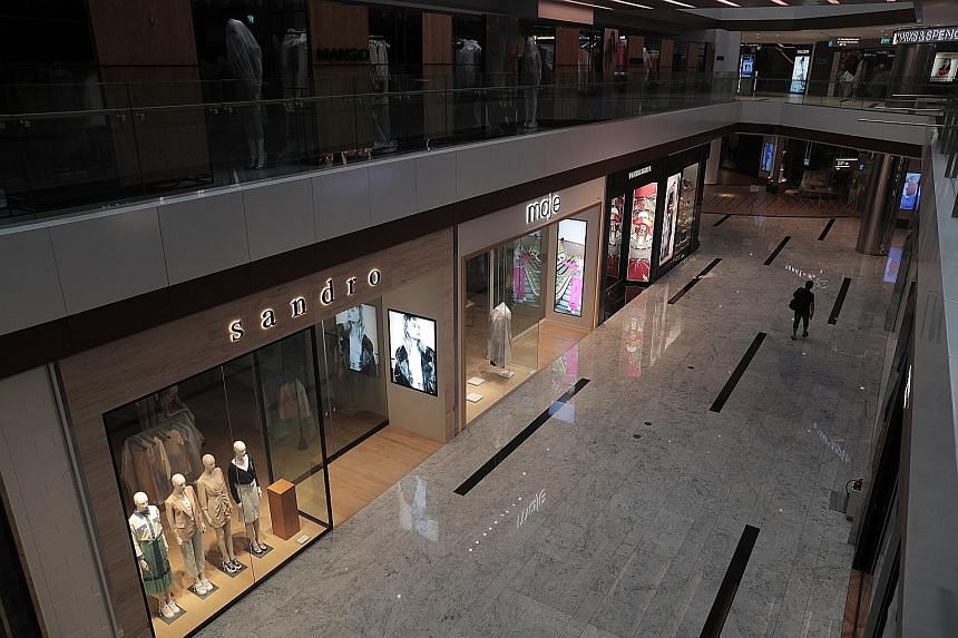 An almost deserted Raffles City mall at around 5.30pm yesterday. Most workplaces - aside from those offering essential services and in key sectors - are closed until May 4 to break the chain of Covid-19 transmission.