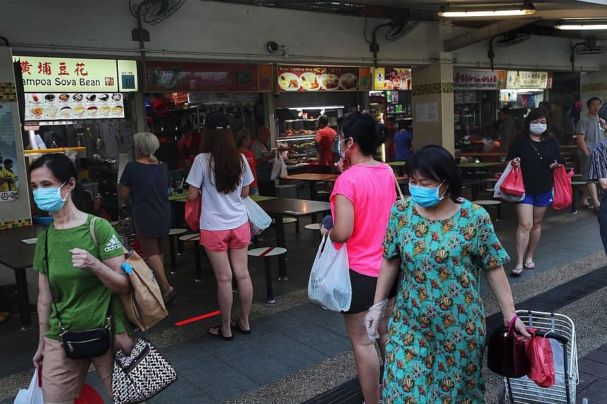 A handwritten sign at an eatery in North Bridge Road reminds customers that they cannot dine in and can buy food only to take away. Fifteen markets, including Geylang Serai Market (above) and Tiong Bahru Market, have set up controlled entry and exit