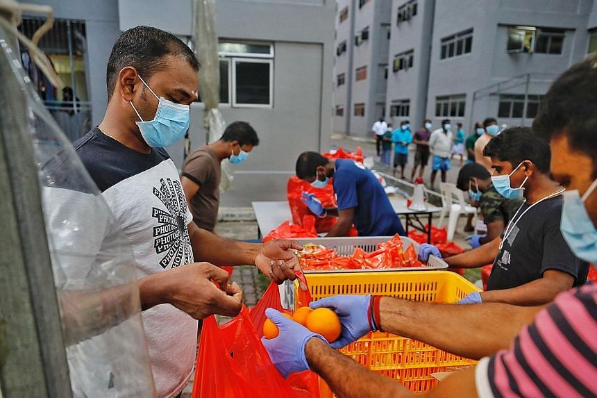 Fruits being distributed to foreign workers under quarantine at Toh Guan Dormitory. The Manpower Ministry said it has taken into account the workers' feedback and increased their meal portions.
