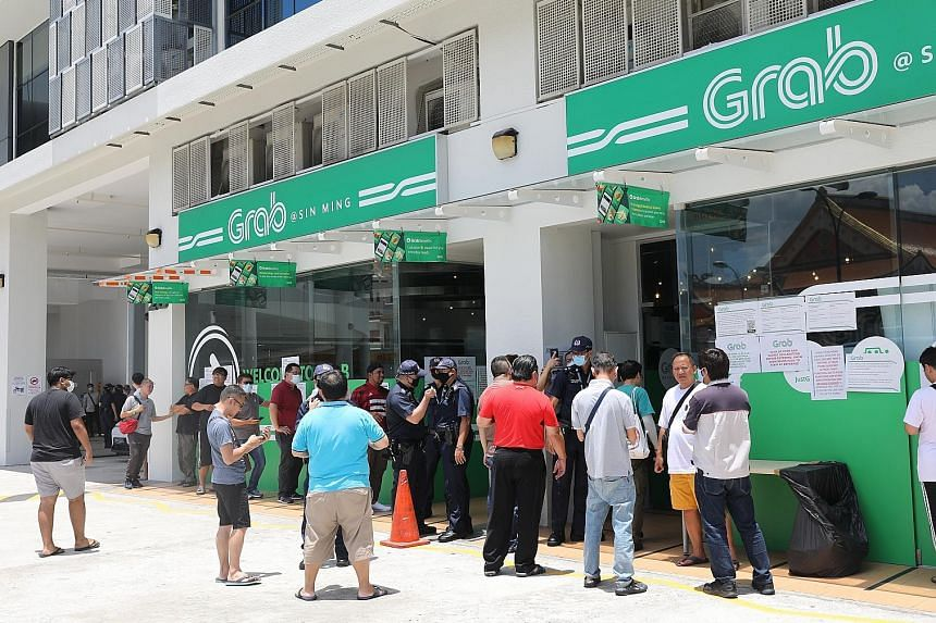 Private-hire drivers outside Grab's office in Sin Ming Lane yesterday, with a few police officers maintaining order. In an update later, Grab said eligible drivers would be able to start delivering food and parcels by the end of the day, even if they