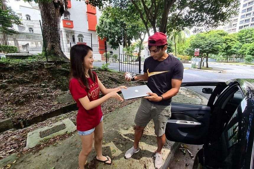 Former national sprinter U.K. Shyam receiving a laptop donated by National University of Singapore medical student Caitlin Wee Fern as part of an initiative to collect devices for less privileged students.