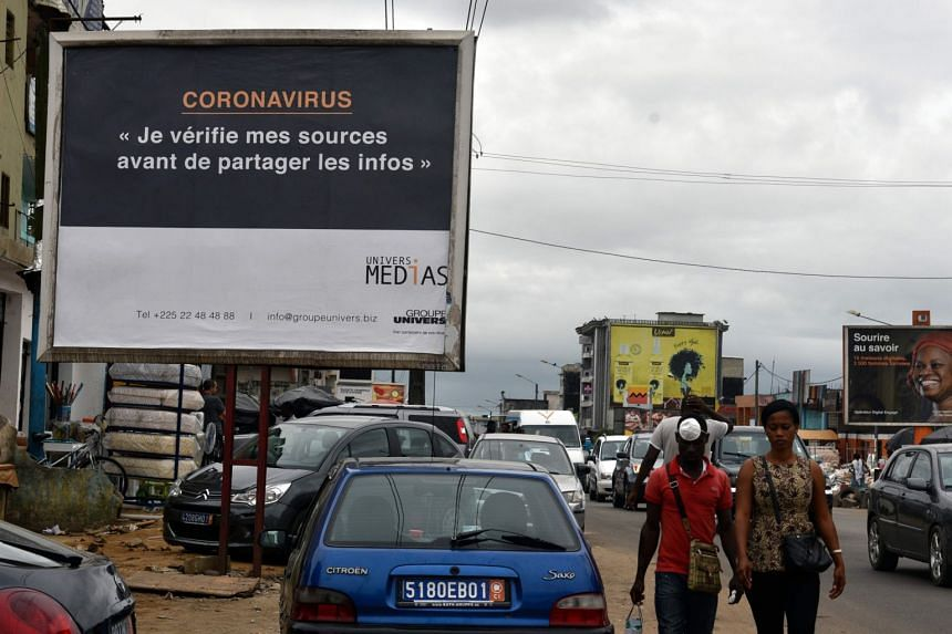 """People walk past a sign reading """"coronavirus - I check my sources before sharing news"""" to warn people about fake news in Abidjan on March 24, 2020."""