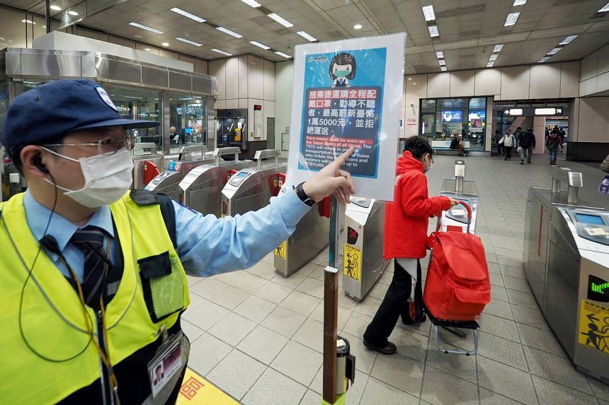 A security guard points to a sign indicating that passengers must wear face mask or be fined at an MRT station in Taipei, Taiwan, on April 5, 2020.