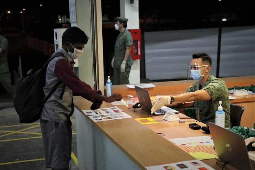 A foreign worker is checked in by an SAF officer before moving into accommodation at an SAF camp.