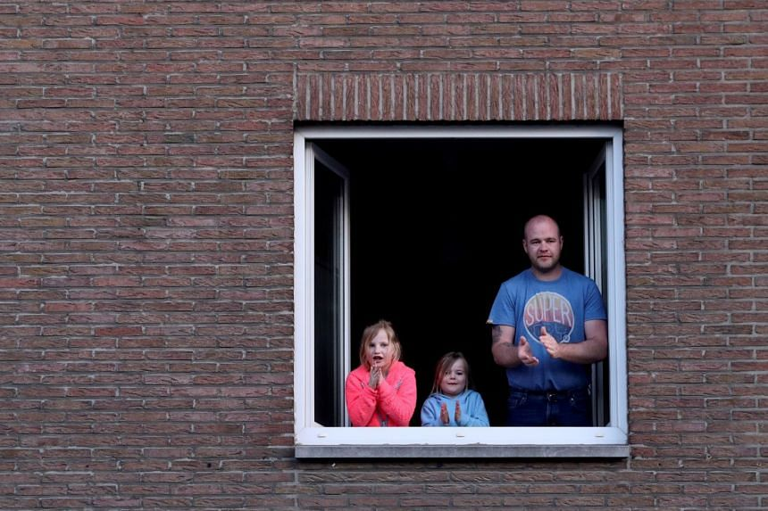 People confined to their homes applaud in support of healthcare workers, during a lockdown in Belgium.