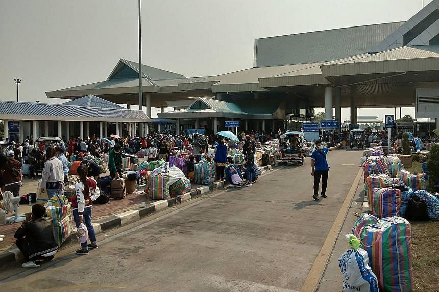 People with their belongings lining up at the immigration post by the second Thai-Lao Friendship Bridge in Mukdahan, waiting to cross into Laos on March 23. PHOTO: AGENCE FRANCE-PRESSE A supermarket employee in Bangkok disinfecting trolleys. Supermar