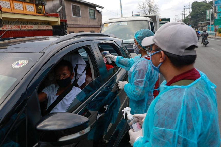 A health worker checks a woman's temperature at a checkpoint in the outskirts of Quezon City, Philippines, on March 15, 2020.