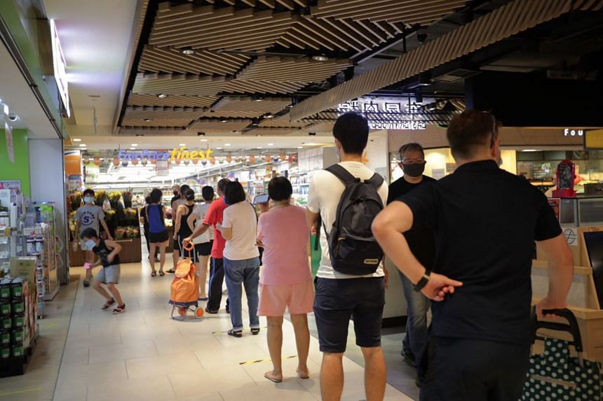 A queue forms outside FairPrice Finest at Clementi Mall around 12.30pm, on April 10, 2020.