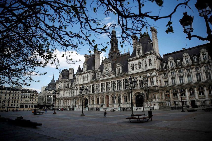 Children play outside Paris' city hall, on April 9, 2020.