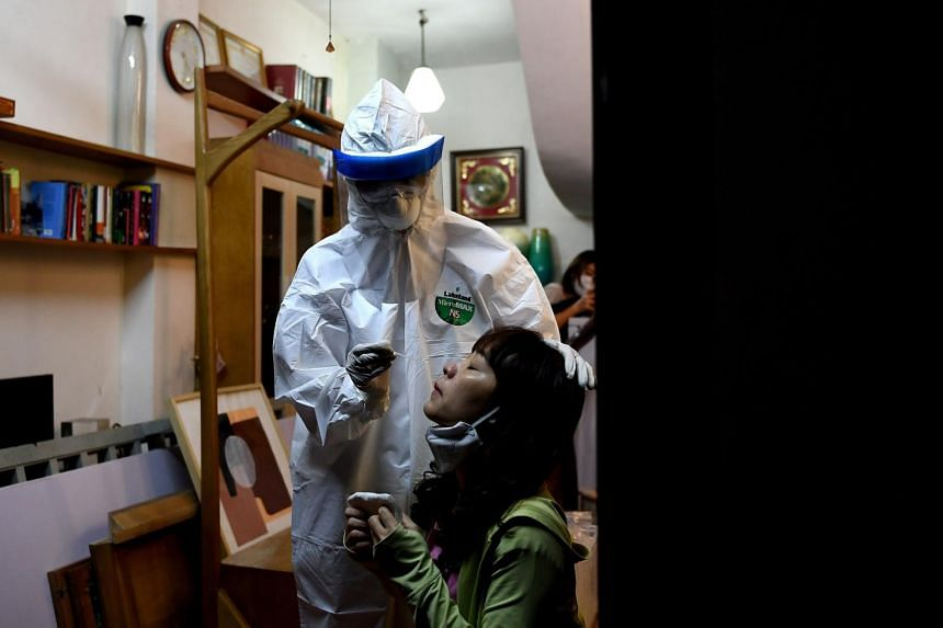 A healthcare worker conducts a swab test on a woman in her house in Hanoi on March 30, 2020.